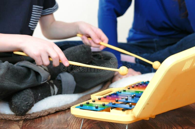 Het spelen muziekinstrument De handen van de close-upjongen ` s op xylofoon met stokken en zijn mammazitting die dichtbij hem spe royalty-vrije stock foto
