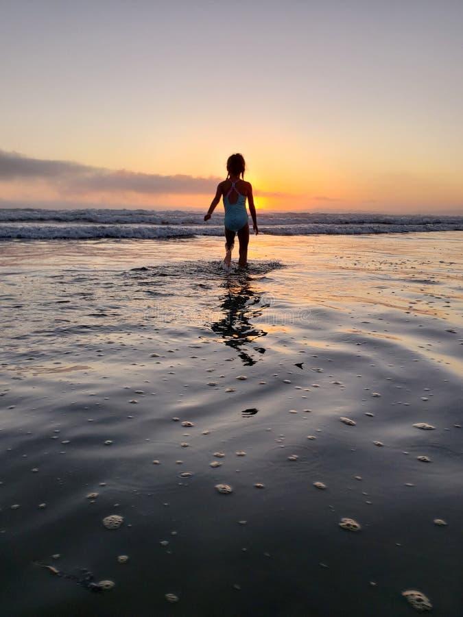 Het spelen in oceaan bij zonsondergang royalty-vrije stock foto's
