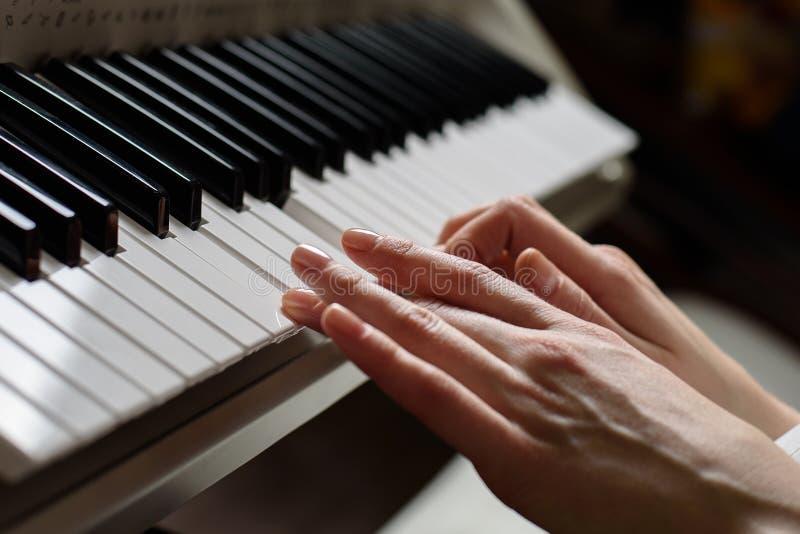 Het spelen op het synthesizerclose-up vrouwen` s handen op de sleutels stock afbeelding