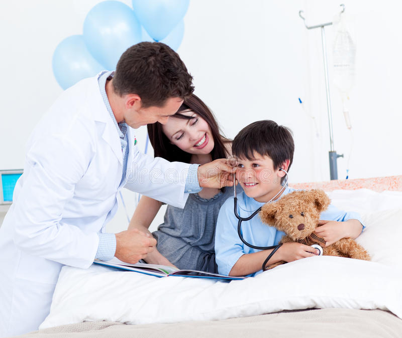 Het spelen van de arts met een kleine jongen en zijn moeder stock foto's