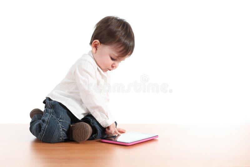 Het spelen van de baby met een digitale tablet stock foto