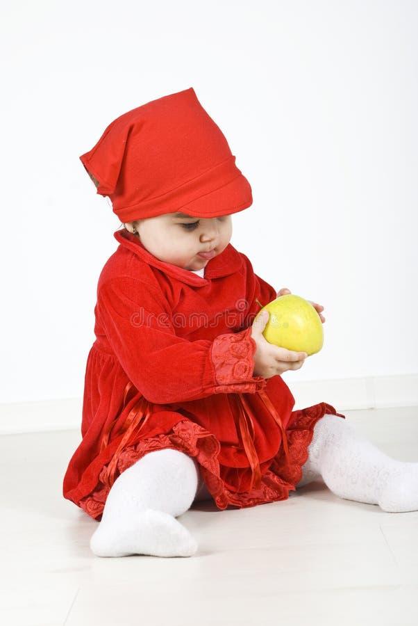 Het spelen van de baby met een groene appel stock fotografie