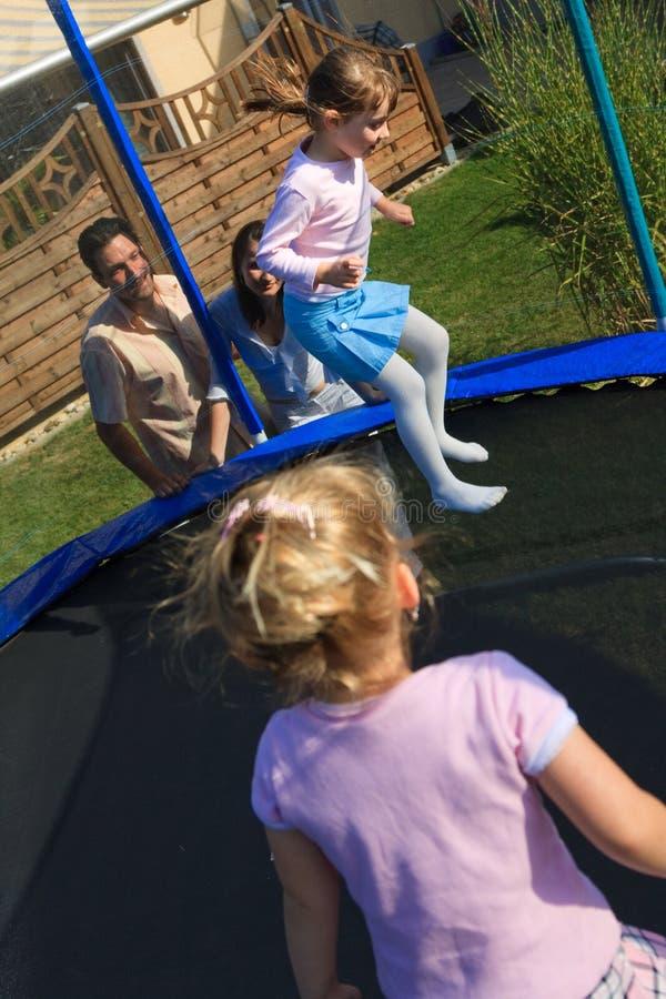 Het Spelen van de familie in de tuin stock foto
