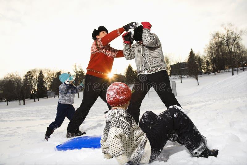 Het spelen van de familie in sneeuw. stock foto