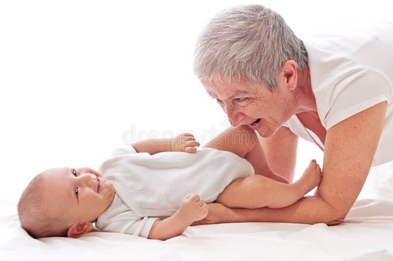 Het spelen van de grootmoeder met een baby stock fotografie