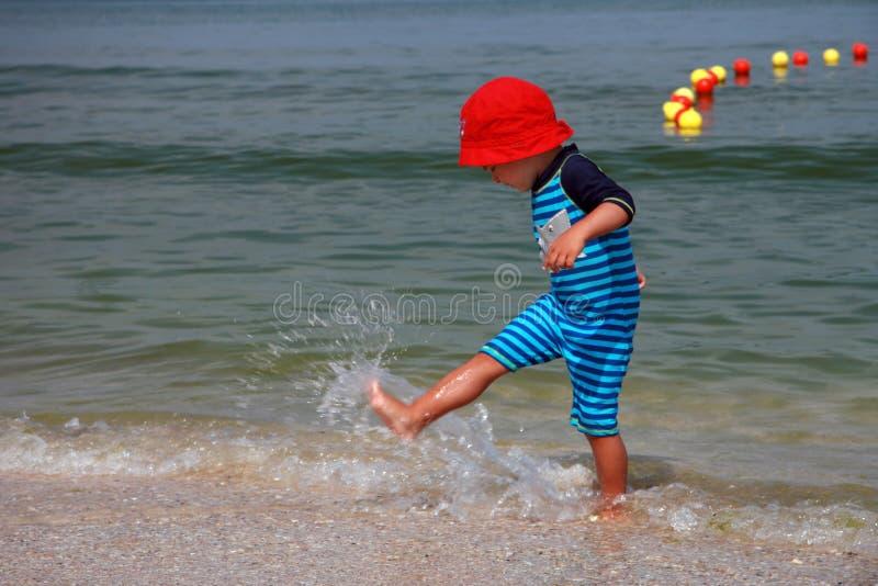 Het Spelen van de jongen in Branding   royalty-vrije stock afbeelding