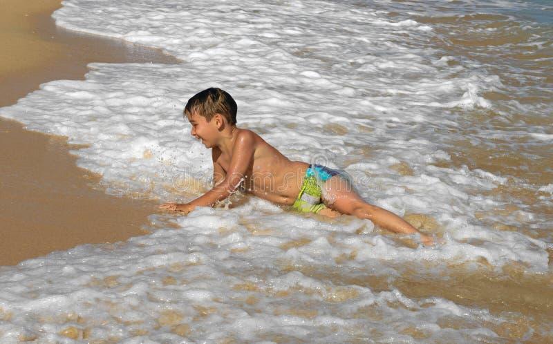 Het spelen van de jongen in de golven stock afbeelding
