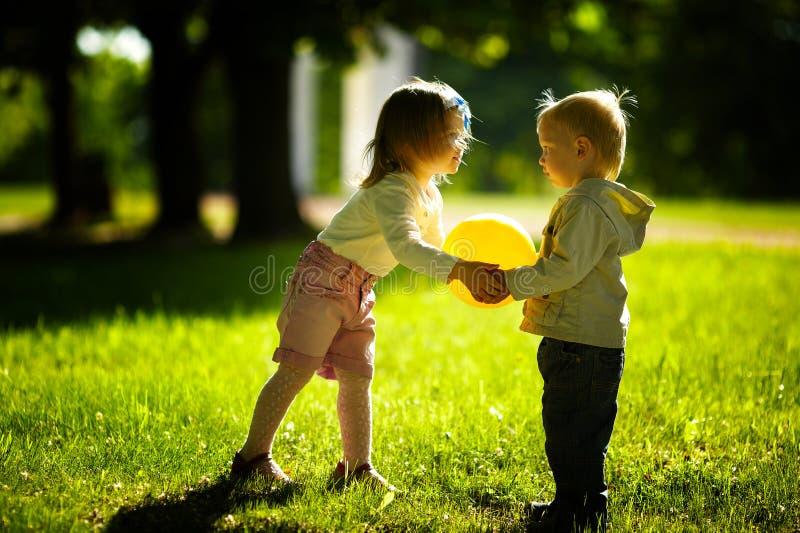 Het spelen van de jongen en van het meisje met bal stock fotografie
