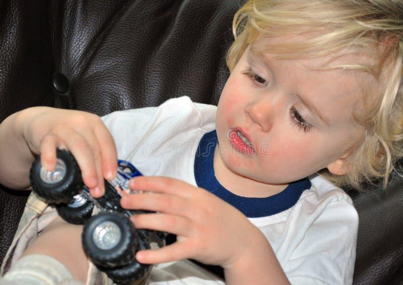 Het spelen van de jongen met auto stock afbeelding