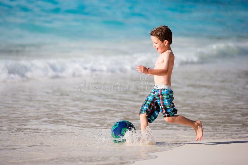 Het spelen van de jongen met bal op strand stock fotografie