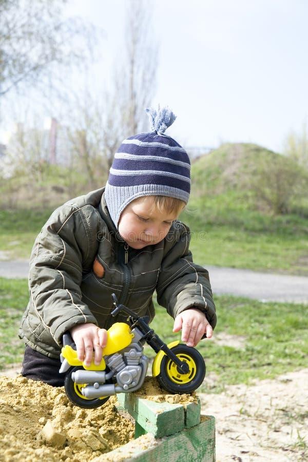 Het spelen van de jongen met een stuk speelgoed stock foto's