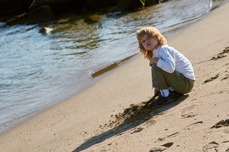 Het spelen van de jongen met het zand op het strand royalty-vrije stock afbeeldingen