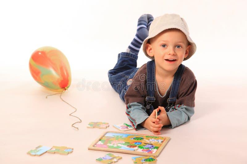 Het spelen van de jongen met raadsel stock foto