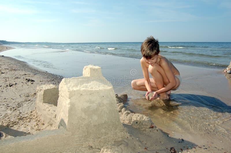 Het spelen van de jongen op het strand stock afbeeldingen