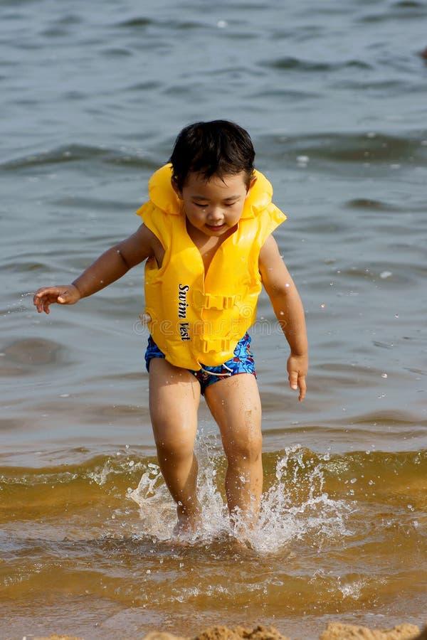Het spelen van de jongen op strand stock foto