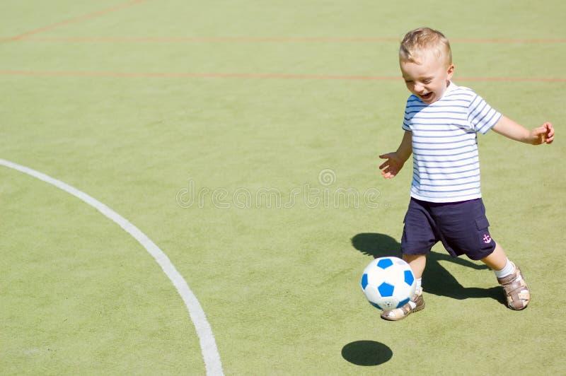 Het spelen van de jongen voetbalstadion royalty-vrije stock afbeeldingen