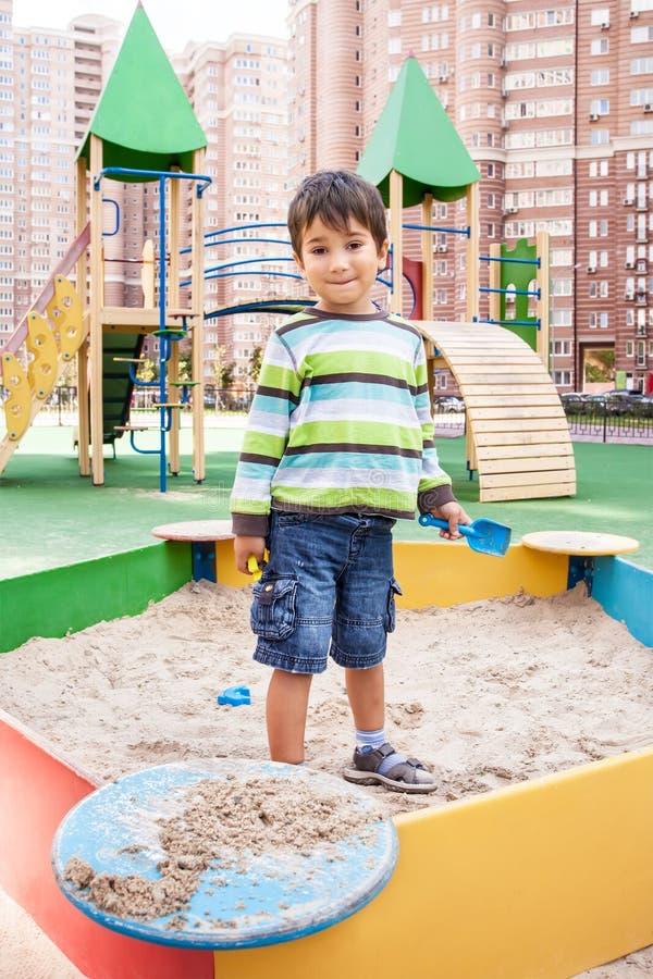 Het spelen van de jongen in zandbak stock fotografie