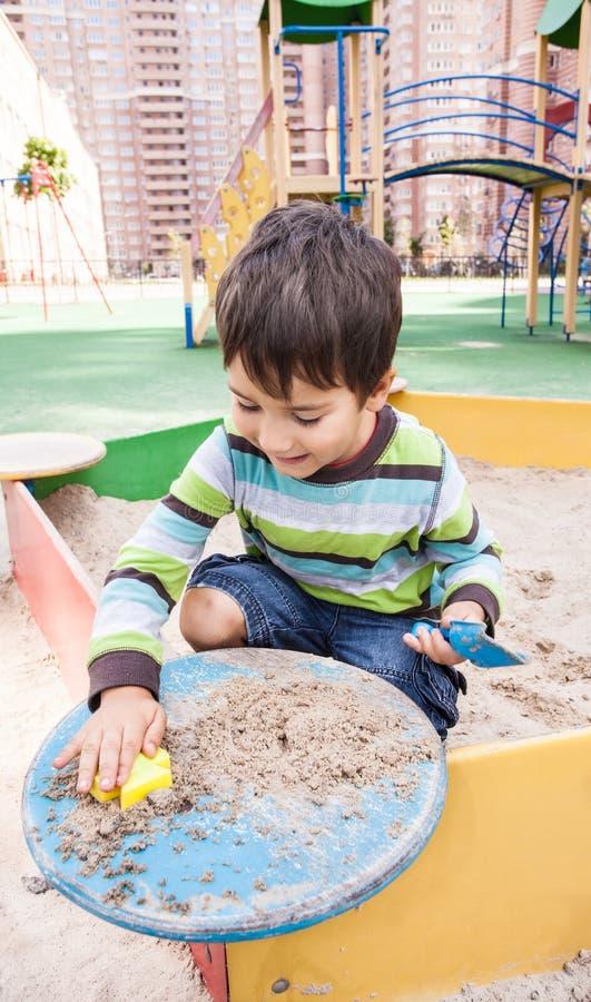 Het spelen van de jongen in zandbak stock foto