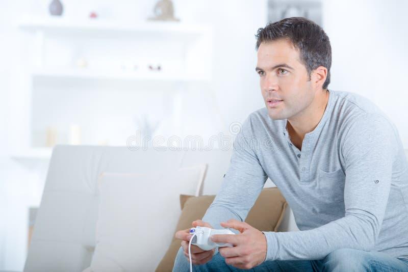 Het spelen van de mens alleen videospelletjes stock afbeeldingen