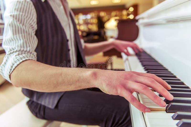 Het spelen van de mens piano stock afbeelding
