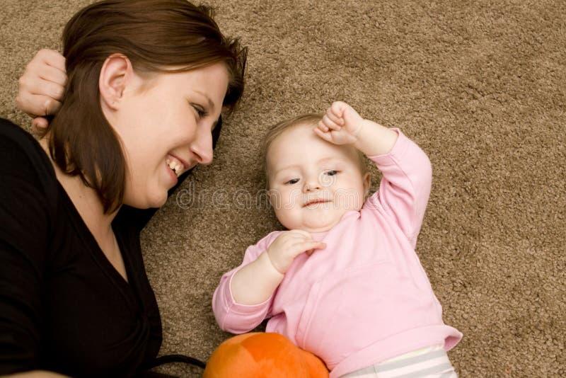 Het spelen van de moeder en van de baby in huis stock afbeeldingen