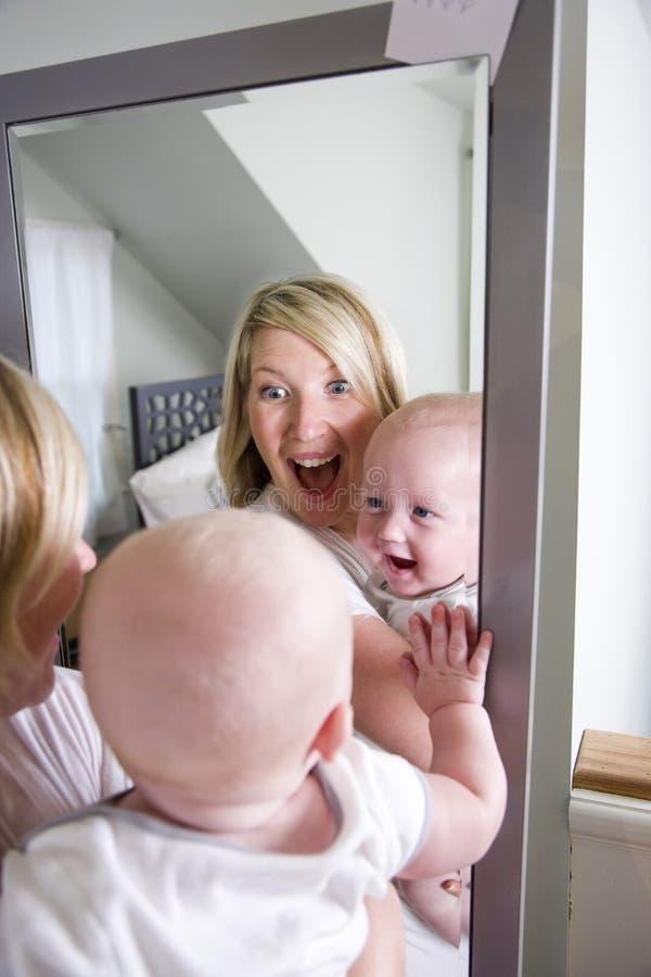 Het spelen van de moeder en van de baby in spiegel stock foto's