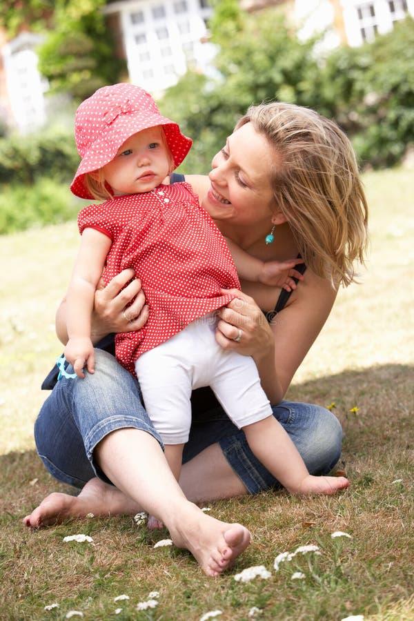 Het Spelen van de moeder en van de Dochter samen in Tuin bij stock fotografie