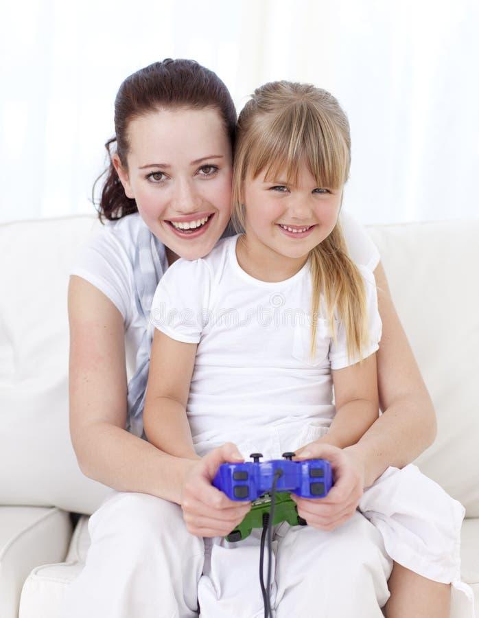 Het spelen van de moeder en van de dochter videospelletjes thuis royalty-vrije stock fotografie