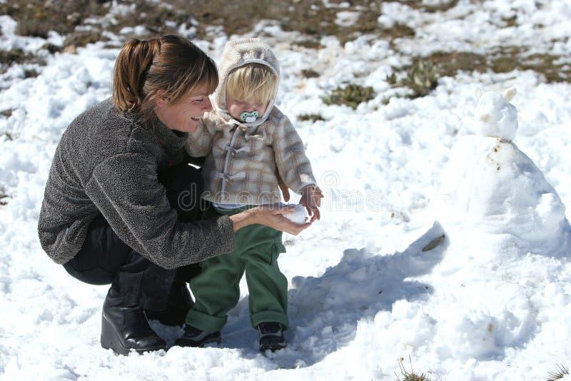 Het Spelen Van De Moeder En Van De Zoon In De Sneeuw En Het Bulding Van Een Sneeuwman Royalty-vrije Stock Afbeeldingen