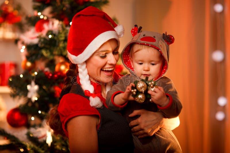 Het spelen van de moeder met baby dichtbij Kerstboom stock foto's