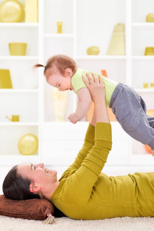 Het spelen van de moeder met haar babymeisje stock foto