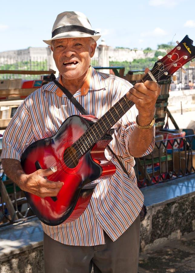 Het spelen van de musicus voor toeristen in Havana stock afbeeldingen