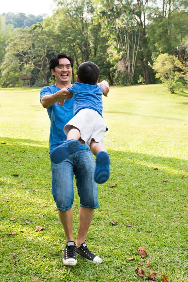 Het spelen van de vader en van de zoon in het park stock foto's