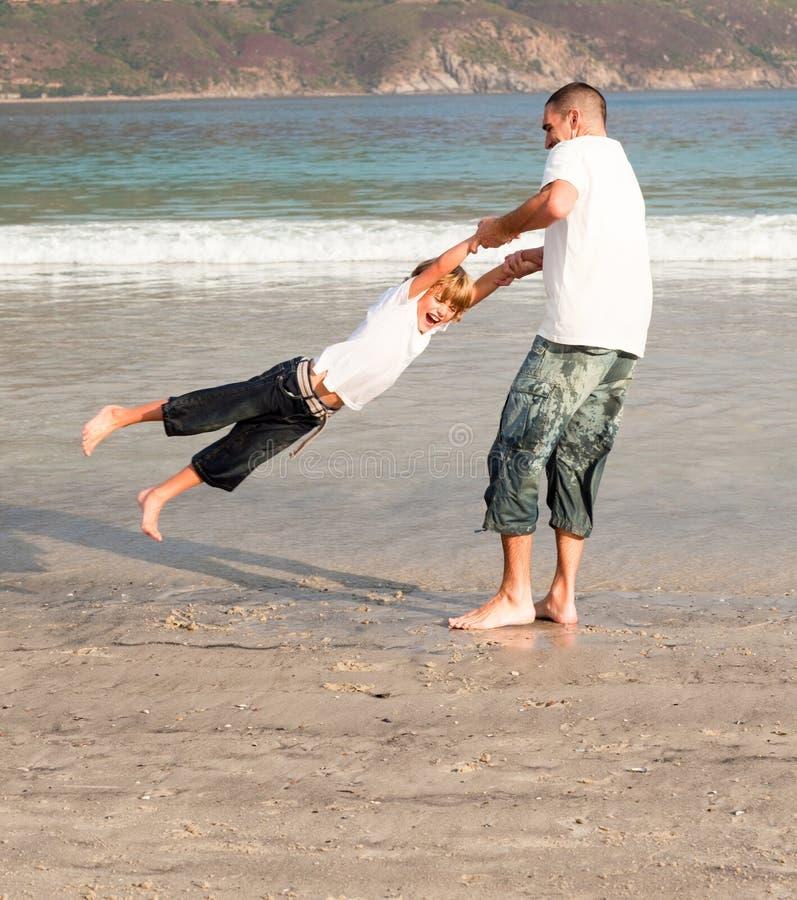Het spelen van de vader en van de zoon op een strand royalty-vrije stock afbeeldingen