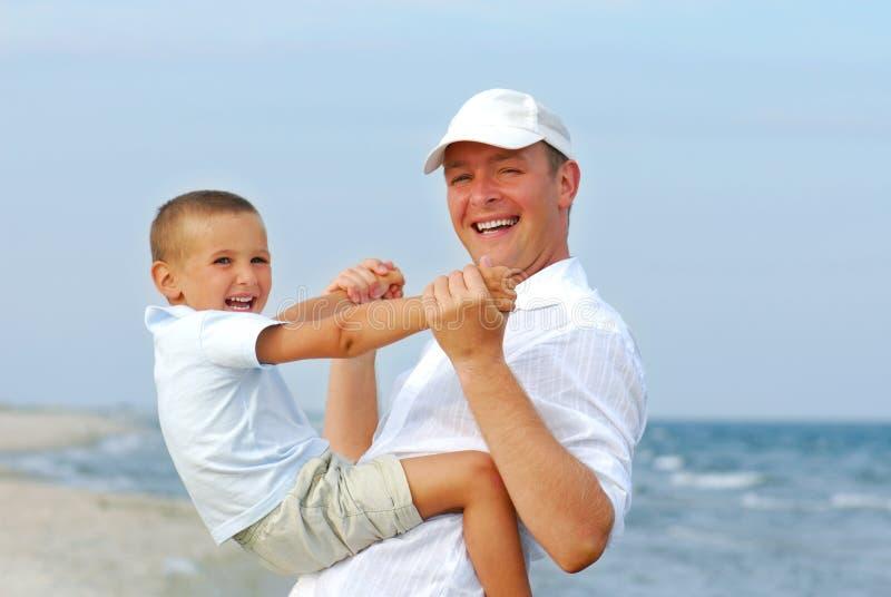 Het spelen van de vader met jonge zoon op het strand stock fotografie