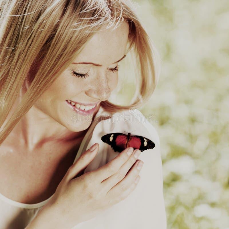 Het spelen van de vrouw met een vlinder royalty-vrije stock fotografie