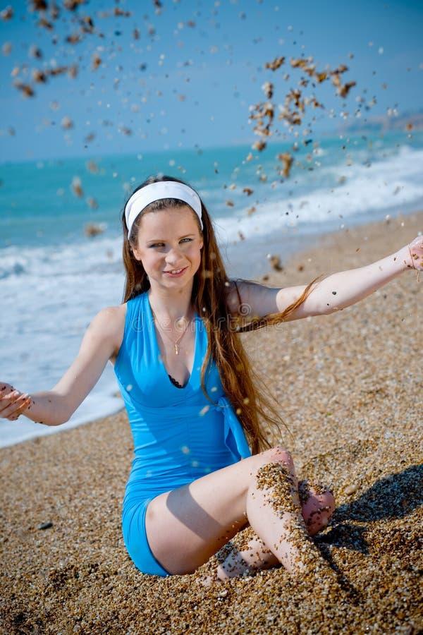 Het spelen van de vrouw met zand bij strand stock fotografie