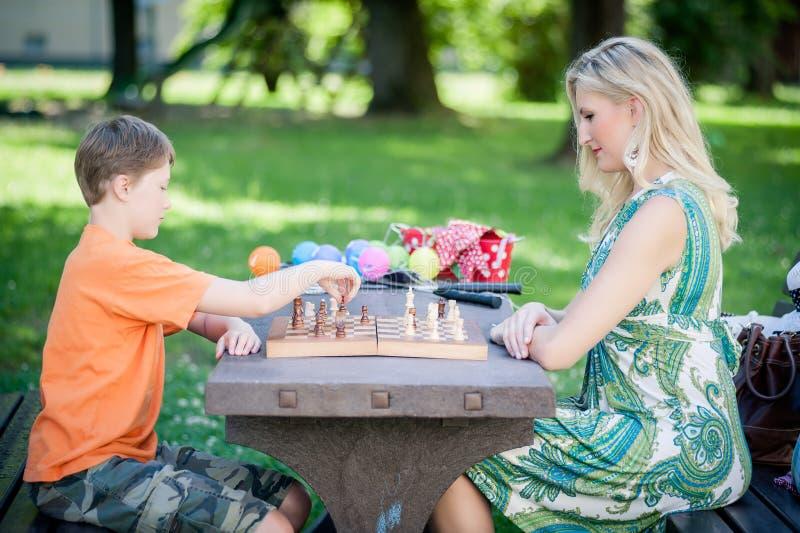 Het spelen van de vrouw Schaak met haar Zoon stock fotografie