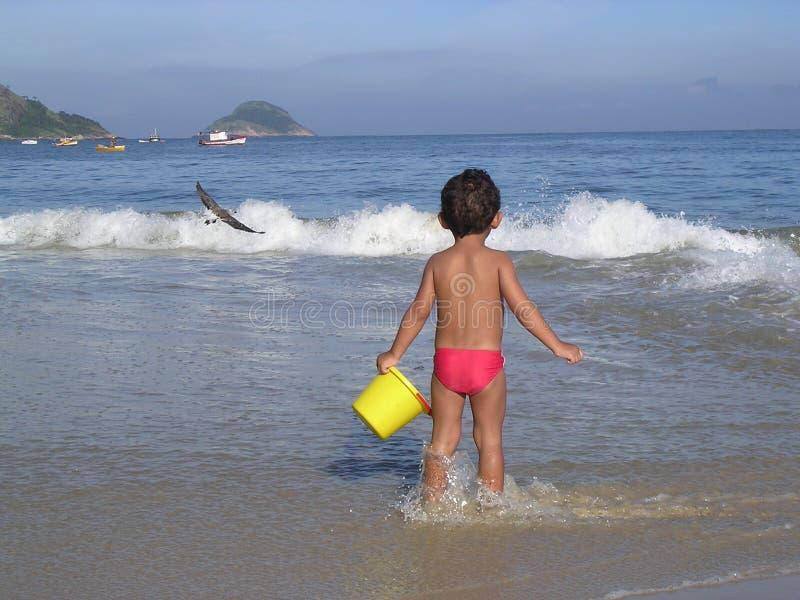 Het spelen van het jonge geitje in het strand stock foto