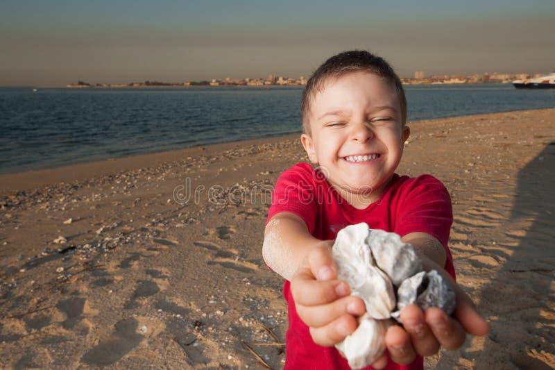 Het spelen van het jonge geitje in het zand bij de rivier royalty-vrije stock afbeelding