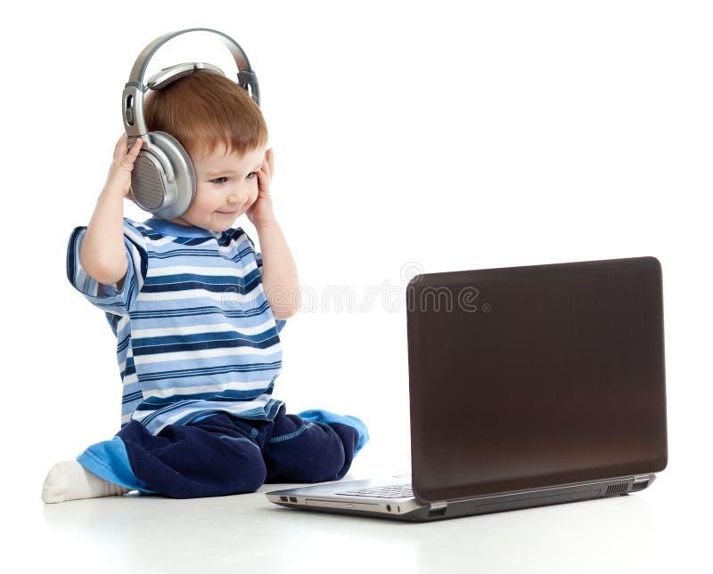 Het spelen van het kind laptop luistert aan muziek in hoofdtelefoons stock fotografie