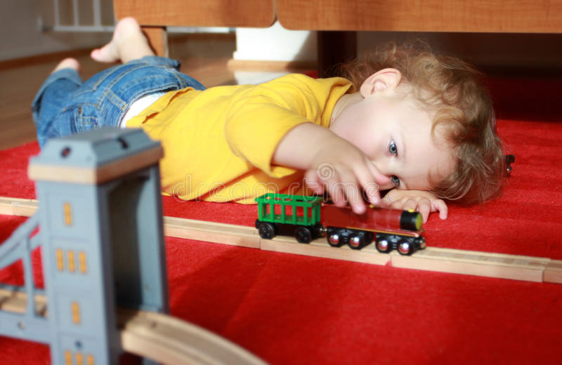 Het Spelen van het kind met Treinen thuis royalty-vrije stock foto's