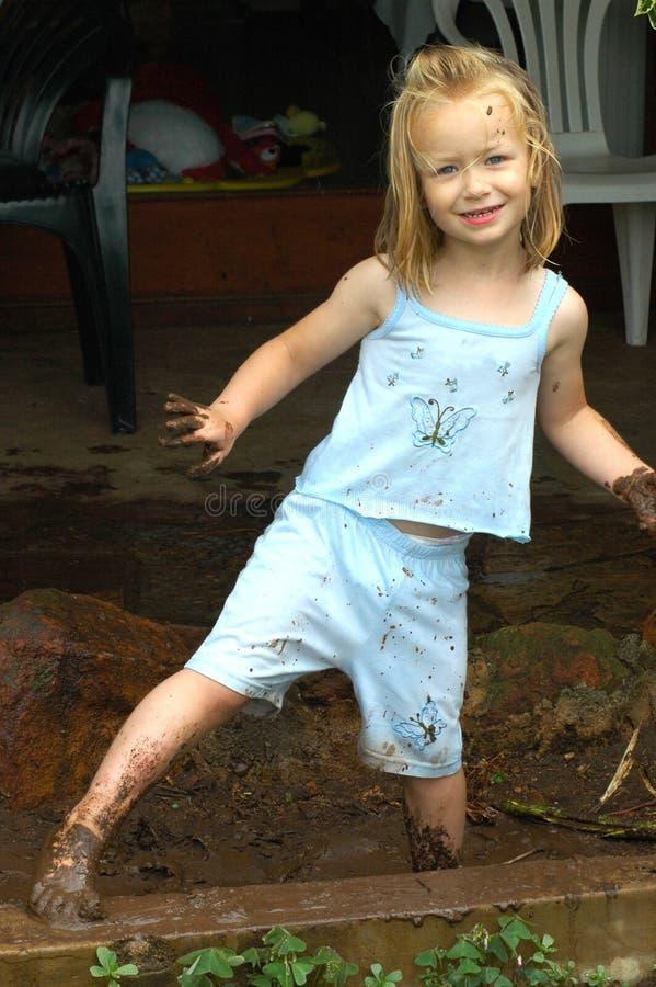 Het spelen van het kind in modder stock afbeeldingen