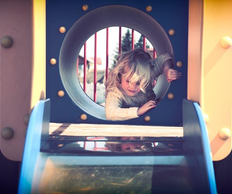 Het spelen van het meisje in de speelplaats stock afbeelding