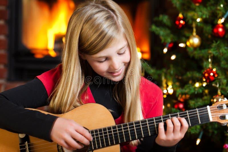 Het spelen van het meisje gitaar op Kerstmisvooravond stock afbeeldingen