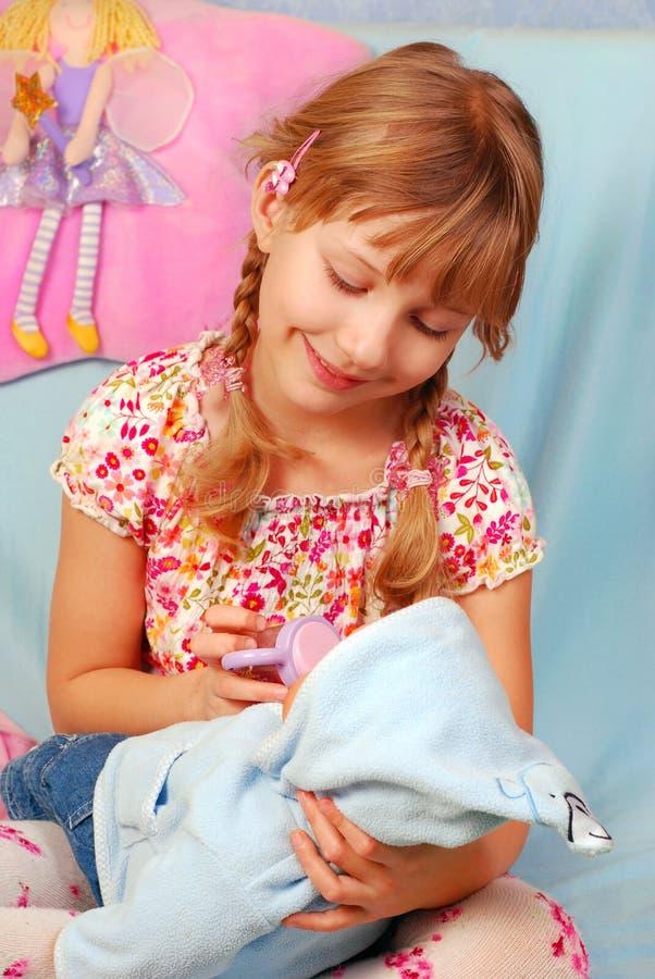 Het spelen van het meisje met baby - pop stock fotografie