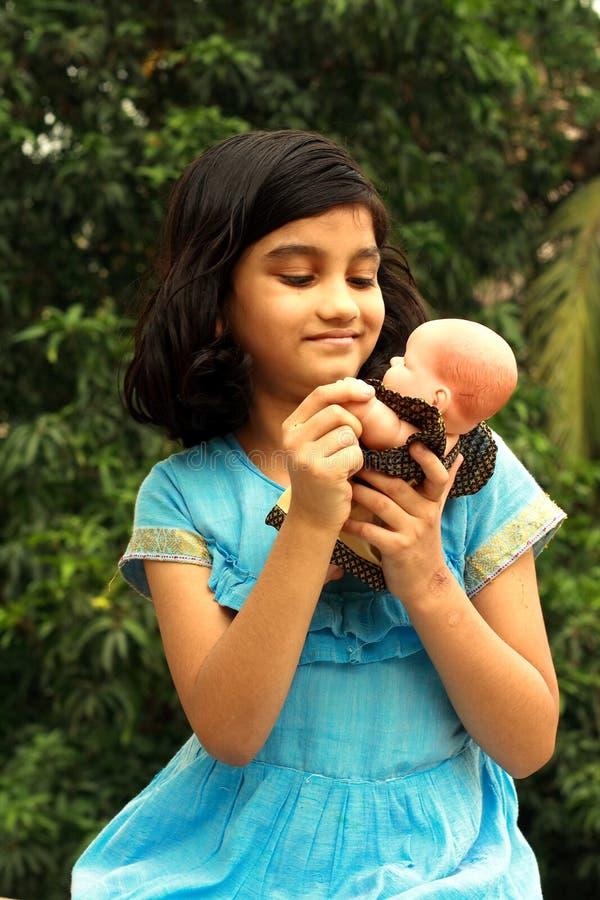 Het spelen van het meisje met haar pop stock afbeelding