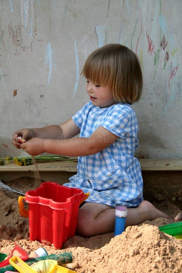 Het spelen van het meisje met het zand stock afbeelding