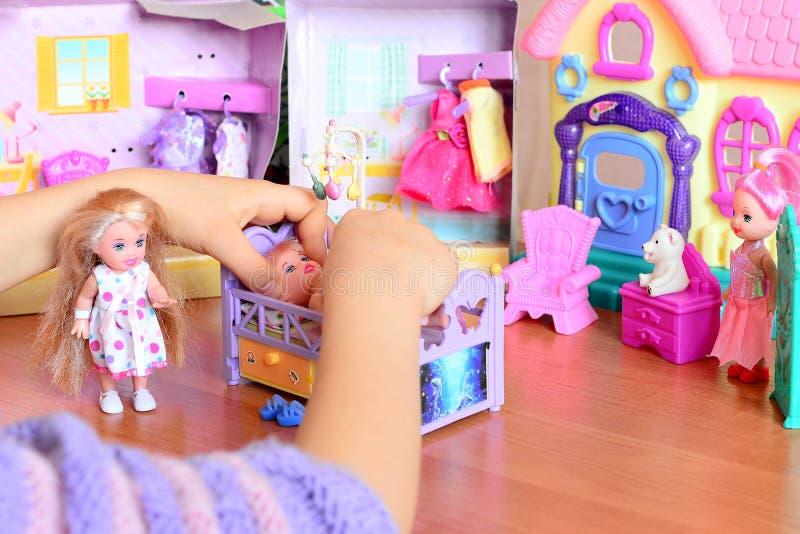Het spelen van het meisje met poppen Het meisje bepaalt een pop aan slaap op een bed Kleurrijk die stuk speelgoed op een lijst wo royalty-vrije stock foto's