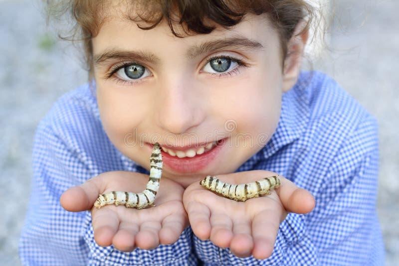 Het spelen van het meisje met zijderups in handen stock fotografie